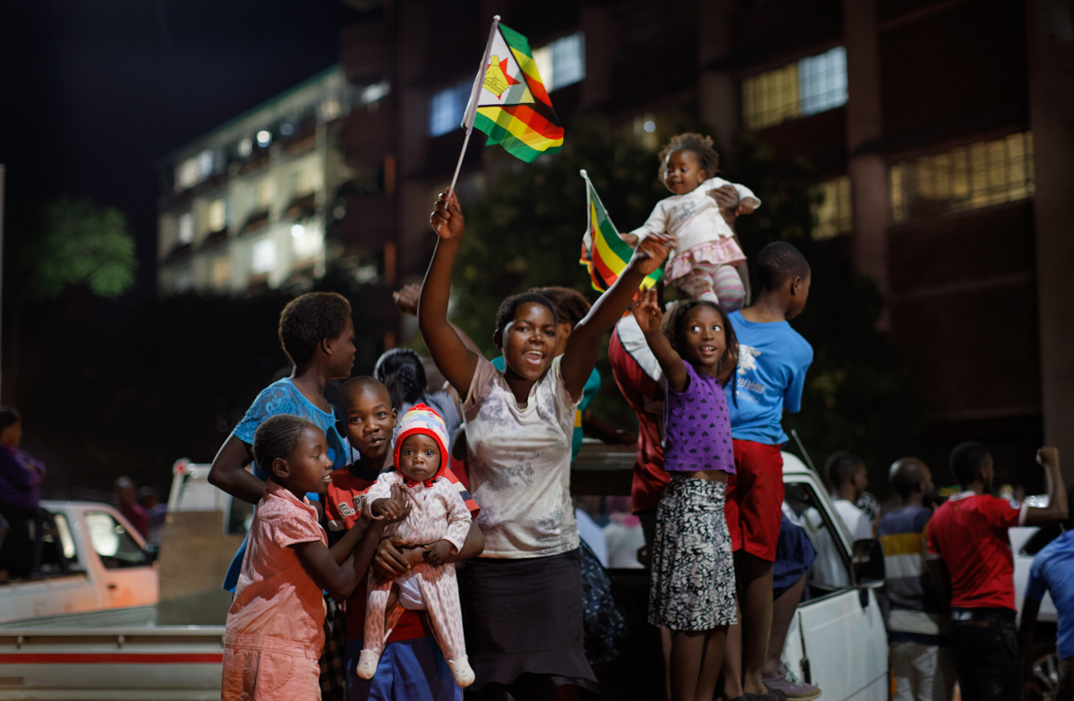 Zimbabweans celebrate at an intersection in downtown Harare. Robert Mugabe resigned as president on Tuesday after 37 years in power, shortly after parliament began impeachment proceedings against him. [Ben Curtis/AP Photo]