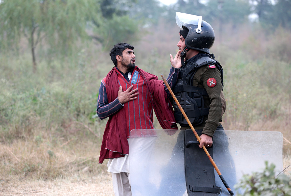 A demonstrator detained by a policeman gestures near the Faizabad junction in Islamabad, Pakistan. [Caren Firouz/Reuters]