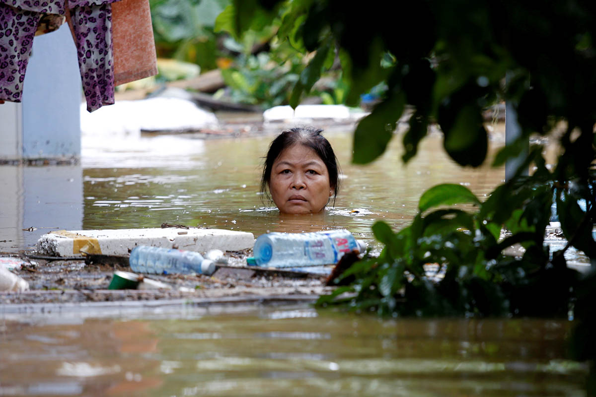 A woman wades through a submerged street in the UNESCO heritage town of Hoi An. The death toll from a typhoon and ensuing floods in Vietnam reached 61 on Monday, and the government said some reservoirs were dangerously near capacity after persistent rain. [Kham/Reuters]