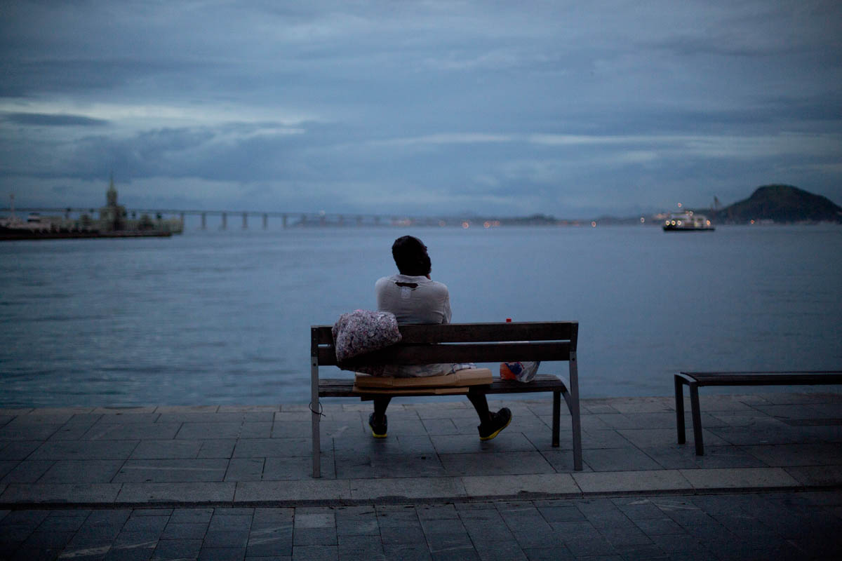 A homeless man sits on a bench after sleeping there in the port area of Rio de Janeiro, Brazil. Many shun shelters because they often have strict rules and, by the city's own acknowledgement, have fallen into disrepair, with infestations of bugs and filthy bathrooms. [Silvia Izquierdo/AP Photo]