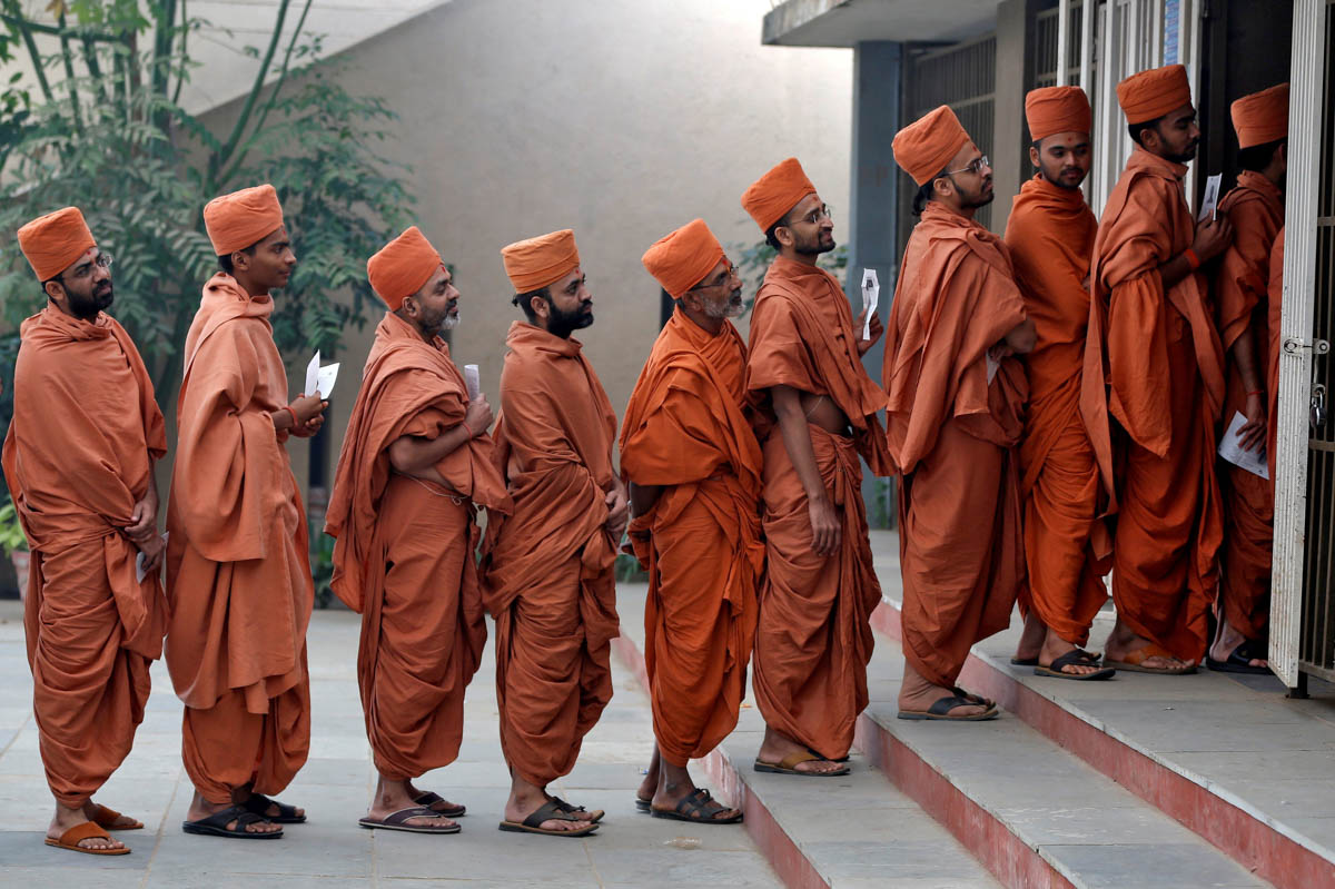Hindu saints queue to cast their votes at a polling station during the last phase of Gujarat state assembly election on the outskirts of Ahmedabad, India. [Amit Dave/Reuters]