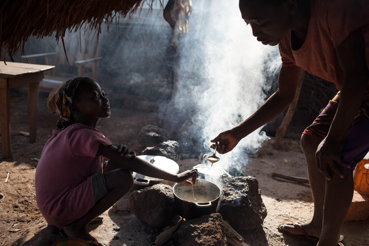 A young girl prepares food for IDPs, some of whom are living between the houses of villagers. [Adrienne Surprenant/Al Jazeera]