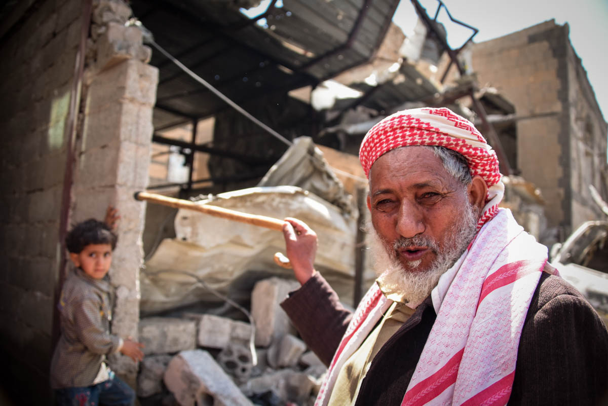 A man points at his house destroyed by air strikes in Sanaa. Destruction in the Yemeni capital is everywhere: houses, health centres, wedding halls, and even children's playgrounds have been targeted by the raids. [Karl Schembri/NRC/Al Jazeera]