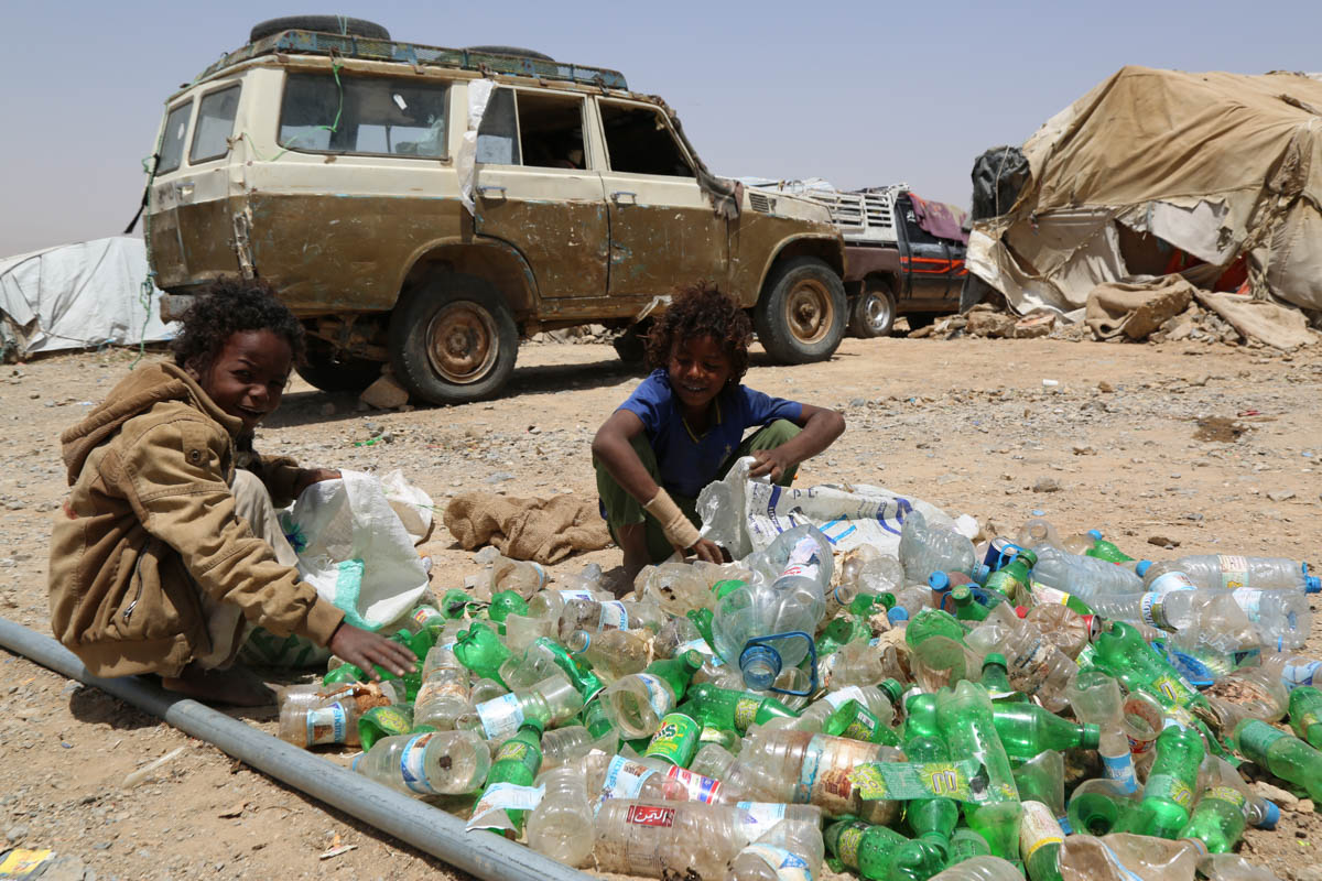 "In this settlement outside Houth, Obaid, 9, (left) and his friend Modrek collect empty plastic bottles to sell for recycling. ""If we collect one full, large bag, we get 150 Yemeni rials [US$0.60],"" said Obaid. ""I used to go to school. I like studying. But there is no school here."" As the war continues, millions of children in Yemen, a country where only 60 percent of the population could read and write before the war, are deprived of an education. [Nuha Mohammed/NRC/Al Jazeera]"