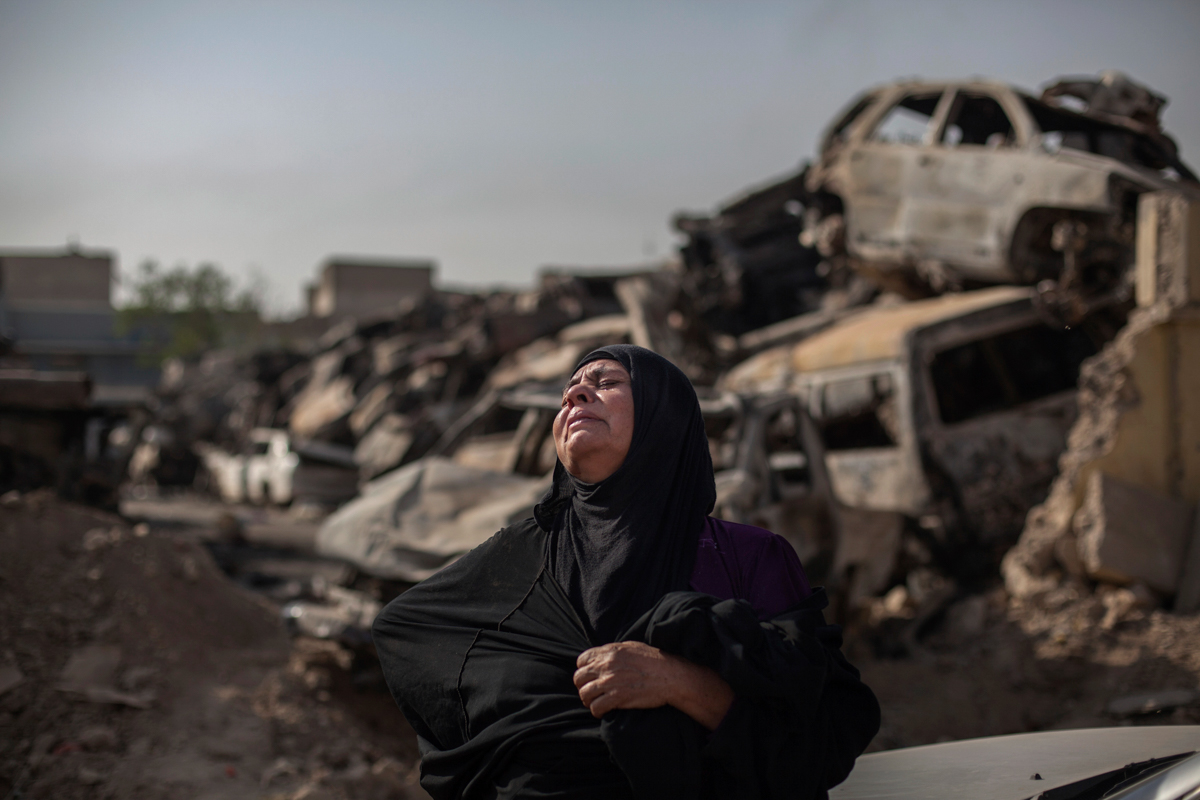 Fatima Ahmed Aswad cries as the body of her 15-year-old daughter, Sana, is exhumed in Mosul for forensic investigation in order to receive a death certificate. The girl died from a mortar attack in the final battle to drive out the Islamic State of Iraq and the Levant group (ISIL, also known as ISIS). [Bram Janssen/AP Photo]