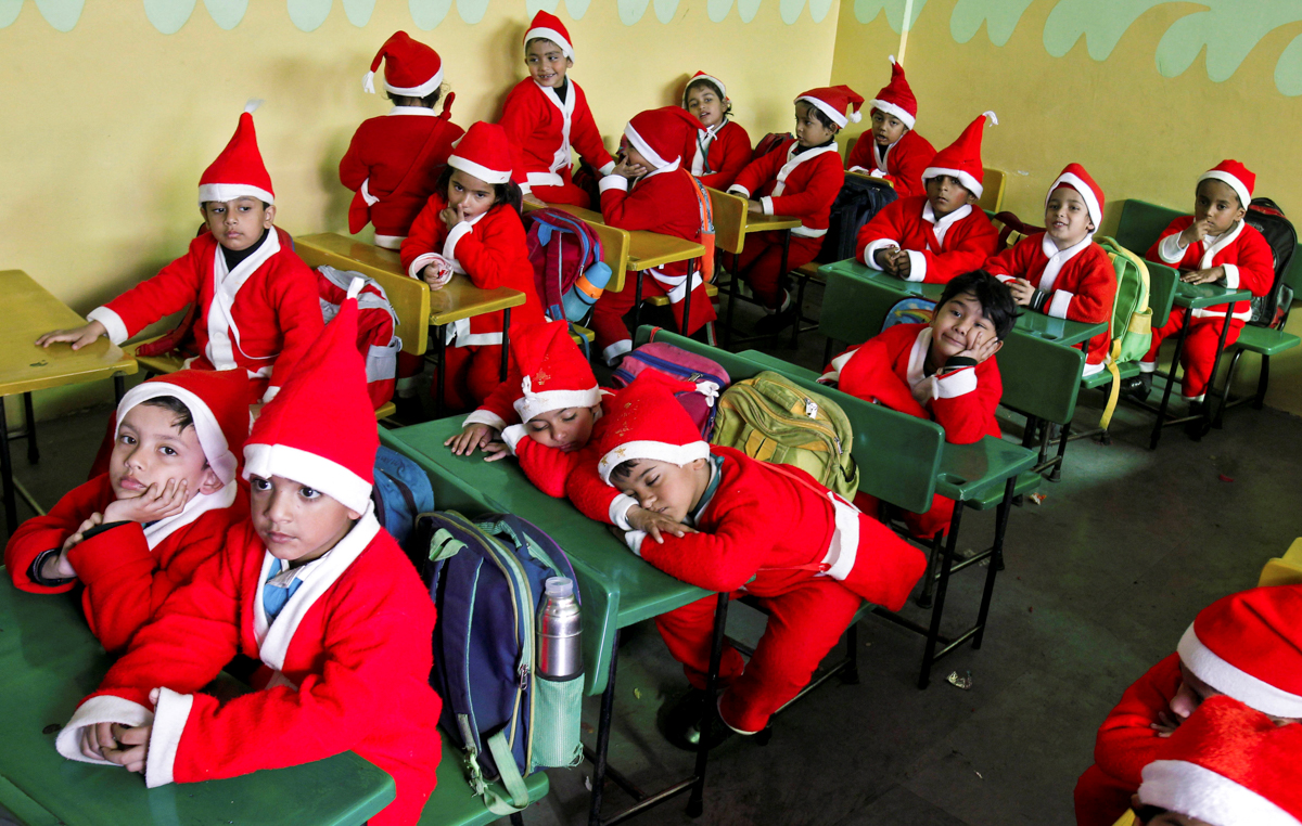 Children dressed in Santa Claus costumes sit inside a classroom before participating in Christmas celebrations at a school in Chandigarh, India. [Ajay Verma/Reuters]