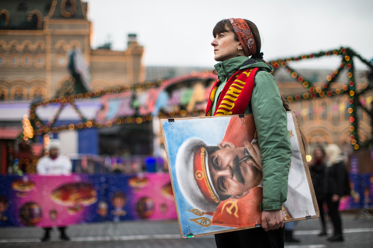 An artist holds a portrait of former Soviet leader Josef Stalin outside the GUM department store, decorated with New Year and Christmas illumination in Moscow's Red Square. Communist supporters marked the anniversary of Stalin's birth on Thursday. [Alexander Zemlianichenko/AP Photo]