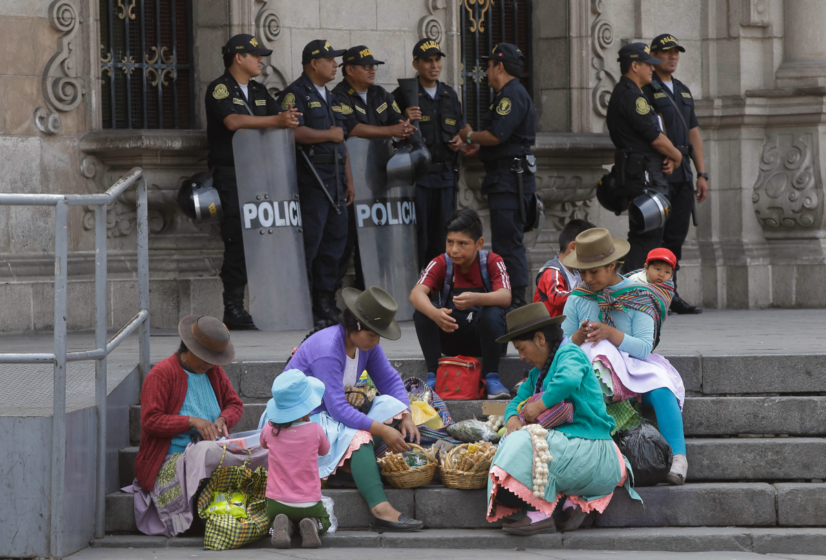 Women prepare to sell candy as police stand guard by the steps of the government palace where impeachment proceedings against Peruvian President Pedro Pablo Kuczynski are going on in Lima, Peru. Congressional opposition leaders initiated the proceedings after an investigative committee revealed documents showing Kuczynski's private consulting firm received payments from Brazilian construction company Odebrecht more than a decade ago. [Martin Mejia/AP Photo]