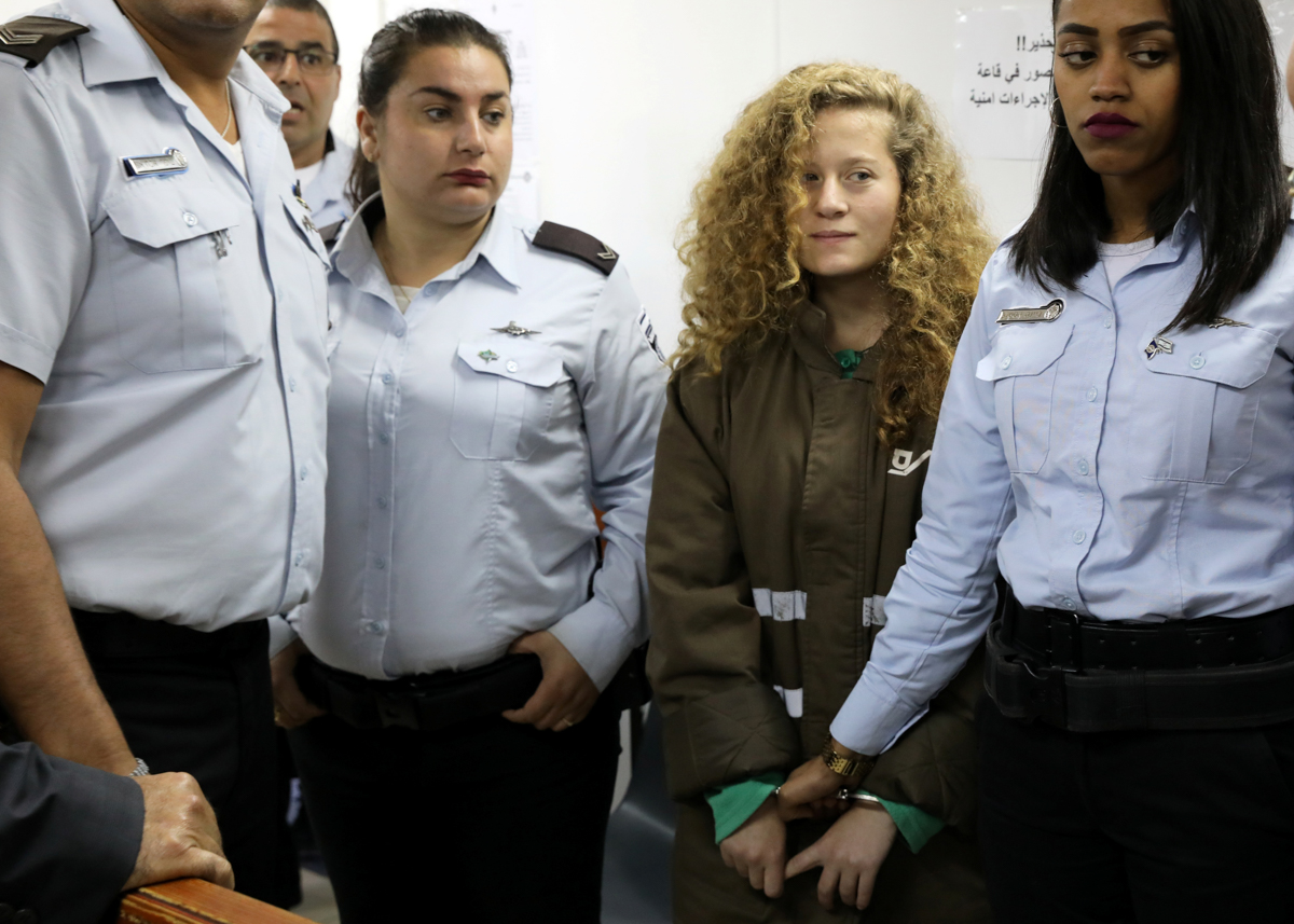 Palestinian teen Ahed Tamimi enters a military courtroom, escorted by Israeli Prison Service personnel near the West Bank city of Ramallah. [Ammar Awad/Reuters]