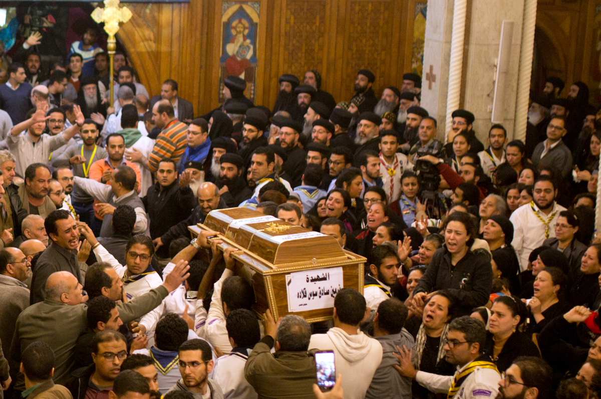 Relatives of Coptic Christians grieve as they carry the coffin of Nermin Sadek, one of the victims of an attack on Mar Mina church, during the funeral service in Cairo, Egypt. At least 10 people, including eight Coptic Christians, were killed after gunmen opened fire outside the church in a south Cairo suburb. [Amr Nabil/AP Photo]