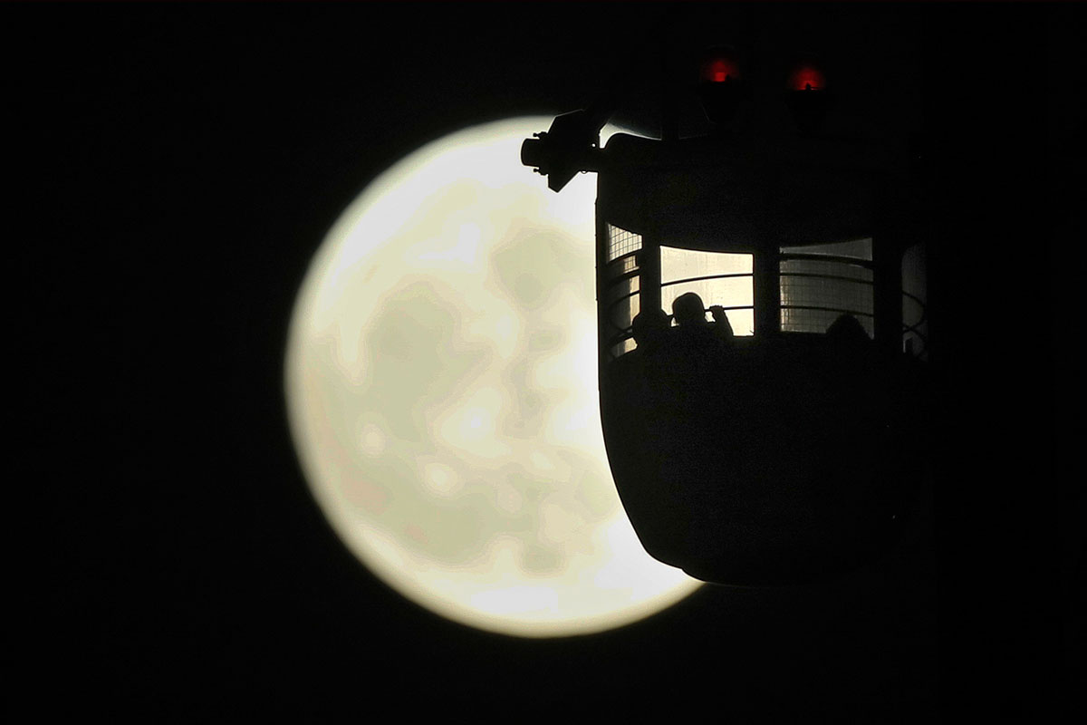 People watch the supermoon from a ferris wheel in Tokyo. [Kimimasa Mayama/EPA-EFE]