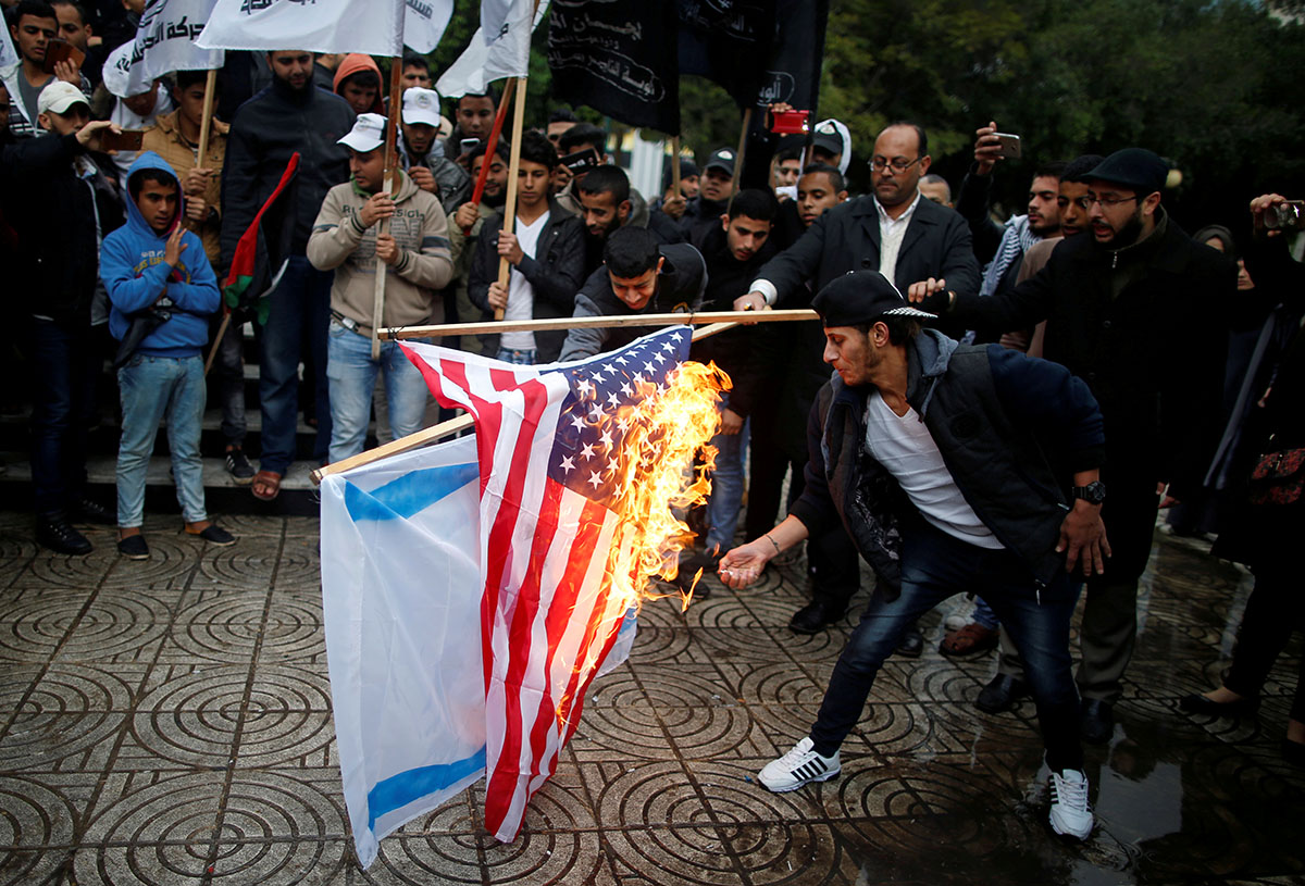 Palestinians burned an Israeli and a US flag during a protest in Gaza City. [Mohammed Salem/Reuters]