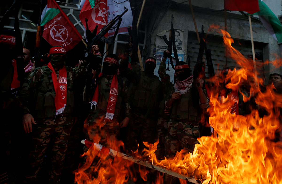 Members of the Popular Front for the Liberation of Palestine burn representations of Israeli and US flags in Gaza City. [Mohammed Salem/Reuters]