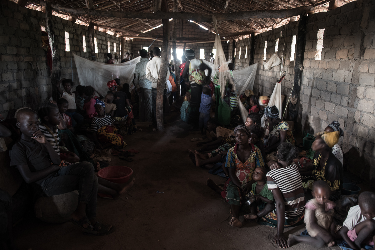 Displaced families are crammed inside the Church of Light in Nyunzu village, in the Democratic Republic of the Congo. Some 100 men, women and children huddle together inside this small, thatched-roof sanctuary, sheltering from torrential rains. [Christian Jepsen/Norwegian Refugee Council/Al Jazeera]