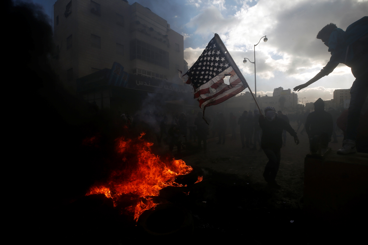 A Palestinian protester prepares to burn a US flag during clashes with Israeli troops at a protest against US President Donald Trump's decision to recognise Jerusalem as the capital of Israel, near the occupied West Bank city of Ramallah. [Mohamad Torokman/Reuters]