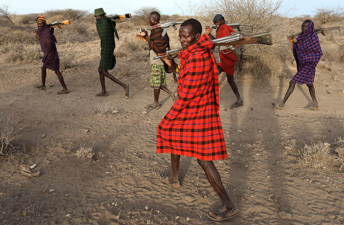 Turkana tribesmen walk with guns in order to protect their cattle from rival Pokot and Samburu tribesmen near Baragoi, Kenya. [Goran Tomasevic/Reuters]
