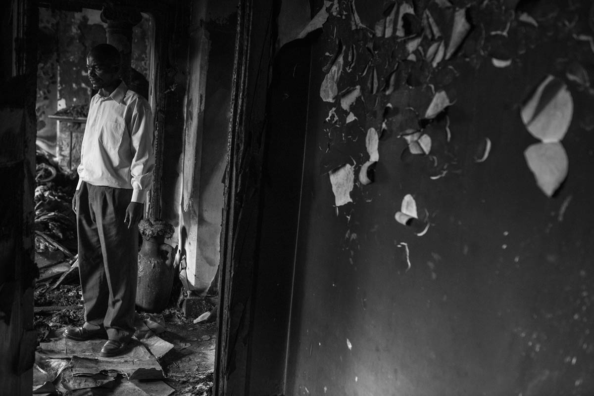 Anderson Mapata, a migrant from Malawi, is seen in a home destroyed in an arson attack in the Johannesburg suburb of Rosettenville. [Ihsaan Haffejee/Al Jazeera]