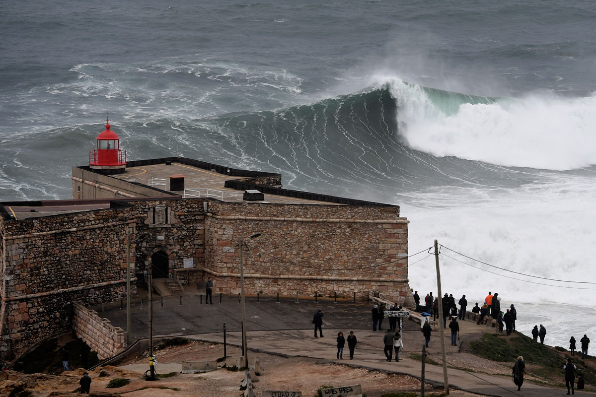 Storm-driven waves approaching the Sao Miguel Arcanjo fort in Nazare, central Portugal. [Francisco Leong/AFP]