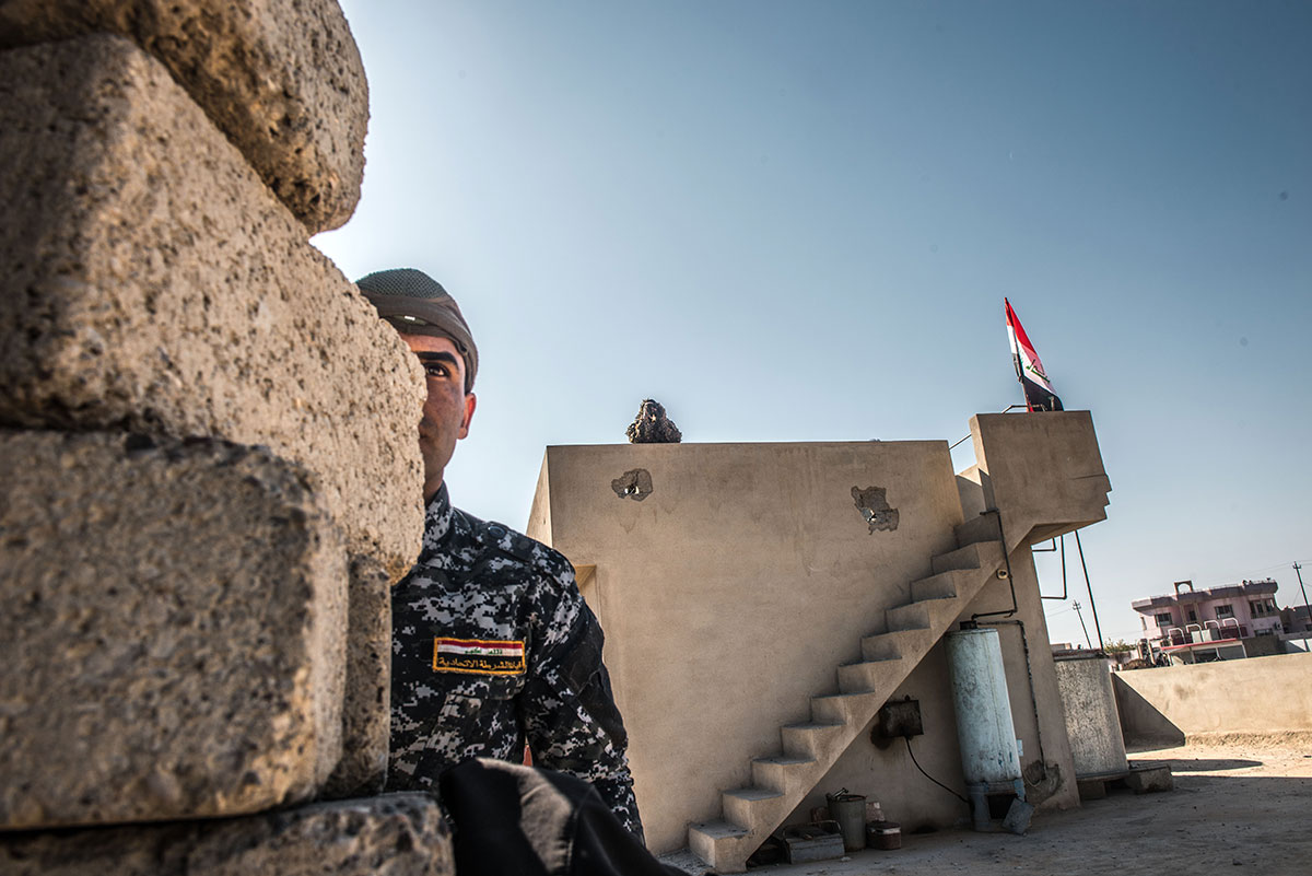 Iraqi police look out over ISIL positions from the frontline village of Albu Saif. Before reaching the city limits, Iraqi forces had to fight their way through a string of small villages. [Tommy Trenchard/Panos/Al Jazeera]