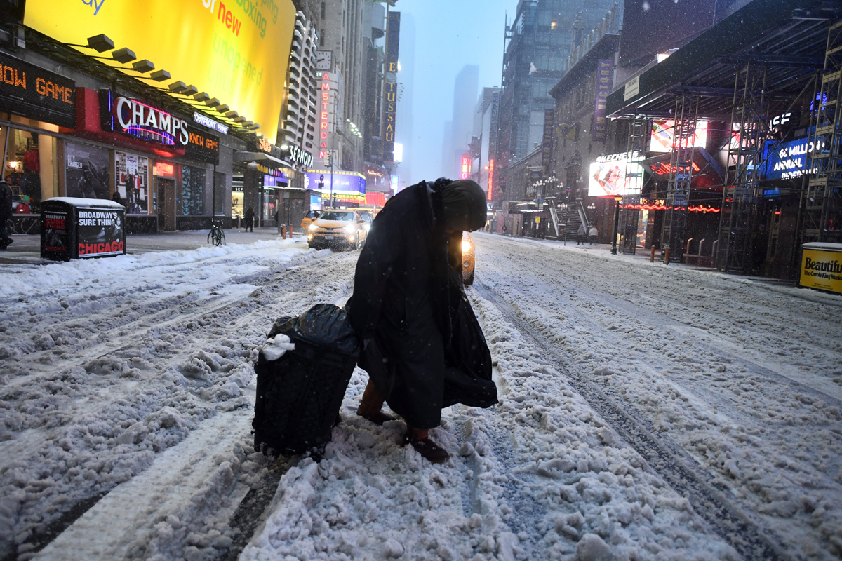 With only minimal ground transportation available in New York City, walking was the only way to get around in the slushy, snowy conditions. [Jewel Samad/AFP]