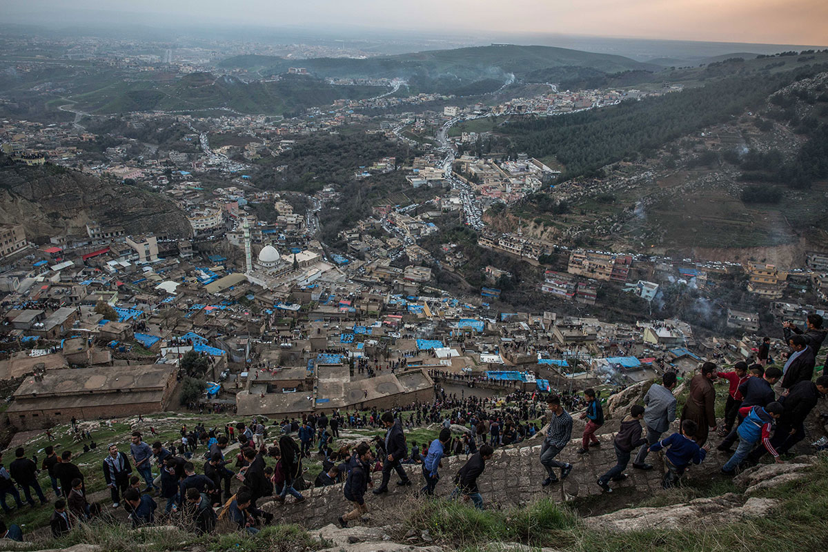 People make their way up a path above  Akre, while others gather on the roofs of buildings below. Most dressed up for the occasion in suits or traditional Kurdish clothing. [John Beck/Al Jazeera]
