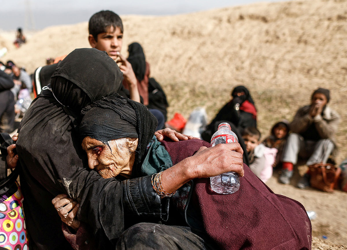 Khatla Ali Abdullah, 90, is embraced after fleeing her home as Iraqi forces battle ISIL in western Mosul. [Zohra Bensemra/Reuters]