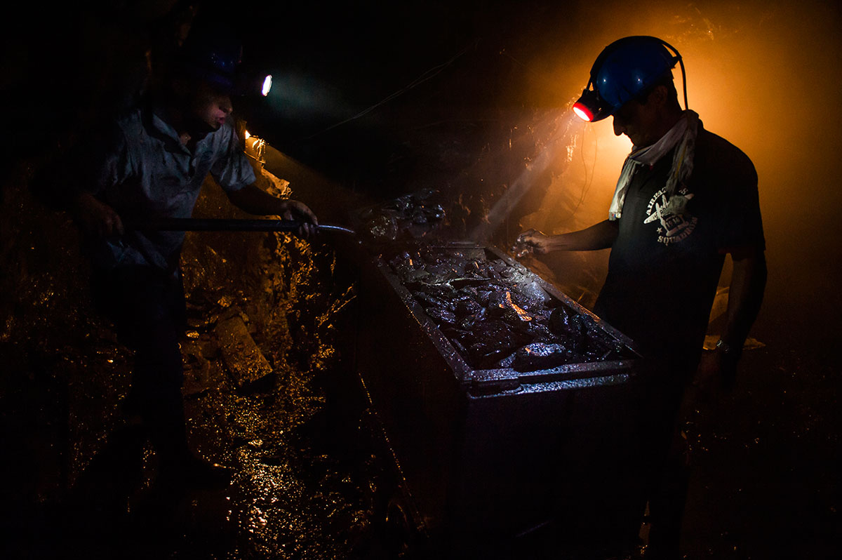 Two miners from an unregulated emerald mine in Pauna, Western Boyaca, look for signs of emeralds in the dark, poorly ventilated mine. [Javier Corso/OAK stories/Al Jazeera]