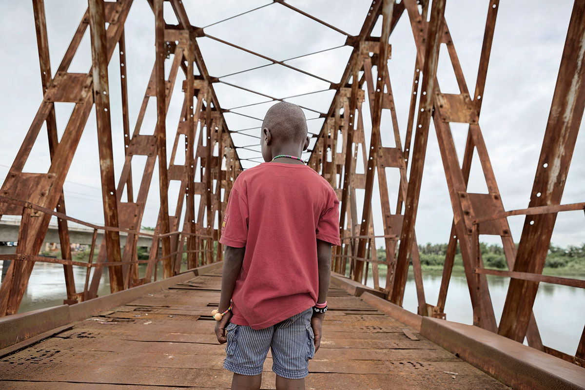 Eight-year-old Justin walks alone over a bridge near Grand-Popo, in Benin. His mother gave him to a shoemaker in her village, where for months he worked as a cobbler. When he stole some money, the shoemaker threw him out. Justin lived on the streets until the police took him to the Centro de Alegria Infantil. The centre is now talking to his family to try to persuade them to take Justin back and to send him to school. [Ana Palacios/Al Jazeera]