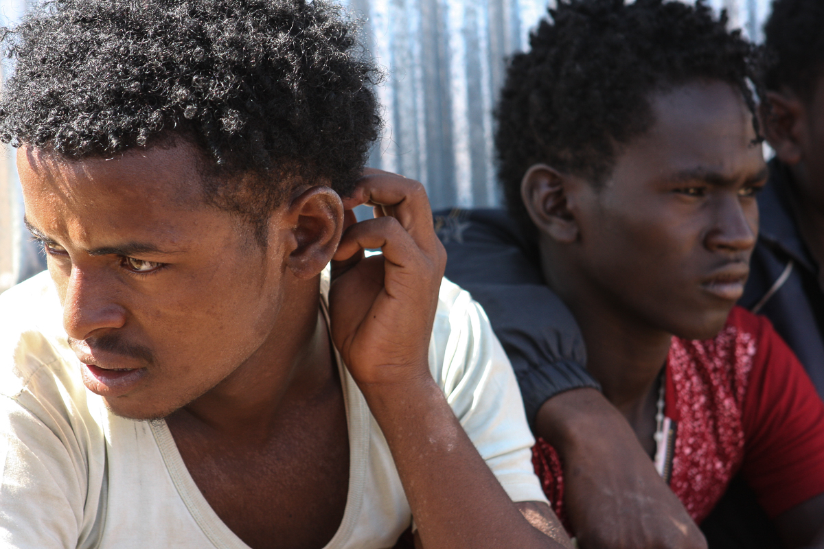 Fifteen Eritrean teenagers and young men, aged from 16 to 20, wait at the Badme entry point to be moved to the screening and registration centre in the town of Endabaguna, 60km west of Aksum, a popular tourist destination. [James Jeffrey/Al Jazeera]
