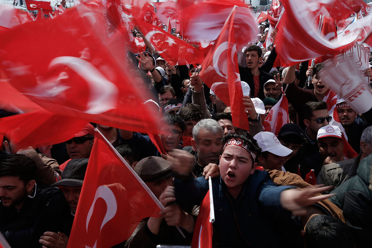Supporters wave national flags as they wait for the arrival of Turkey's President Recep Tayyip Erdogan for a referendum rally in Istanbul. Turkey is heading to a contentious April 16 referendum on constitutional reforms to expand Erdogan's powers. [Emrah Gurel/AP Photo]