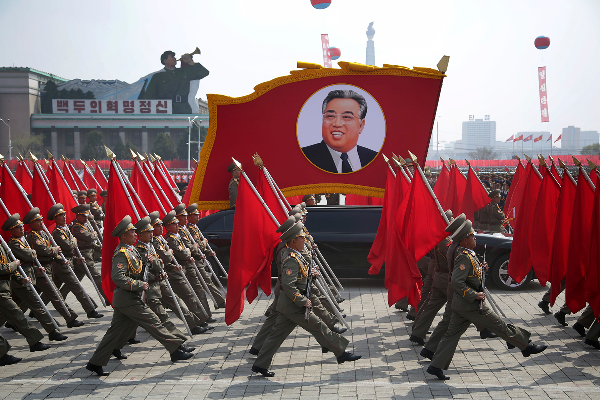 North Korean soldiers carry flags and a photo of late leader Kim Il-sung during a military parade. [Wong Maye-e/AP]