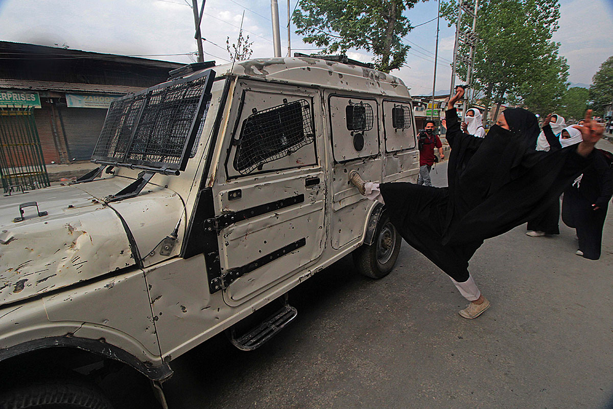 A student kicks a police vehicle during a protest in Srinagar in Indian-administered Kashmir. [Faisal Khan/Al Jazeera]