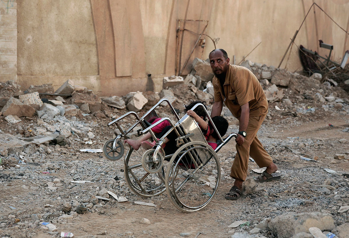 A man pushes two children in a wheelchair as they flee heavy fighting between ISIL and Iraqi special forces in Mosul, Iraq. [Maya Alleruzzo/AP Photo]