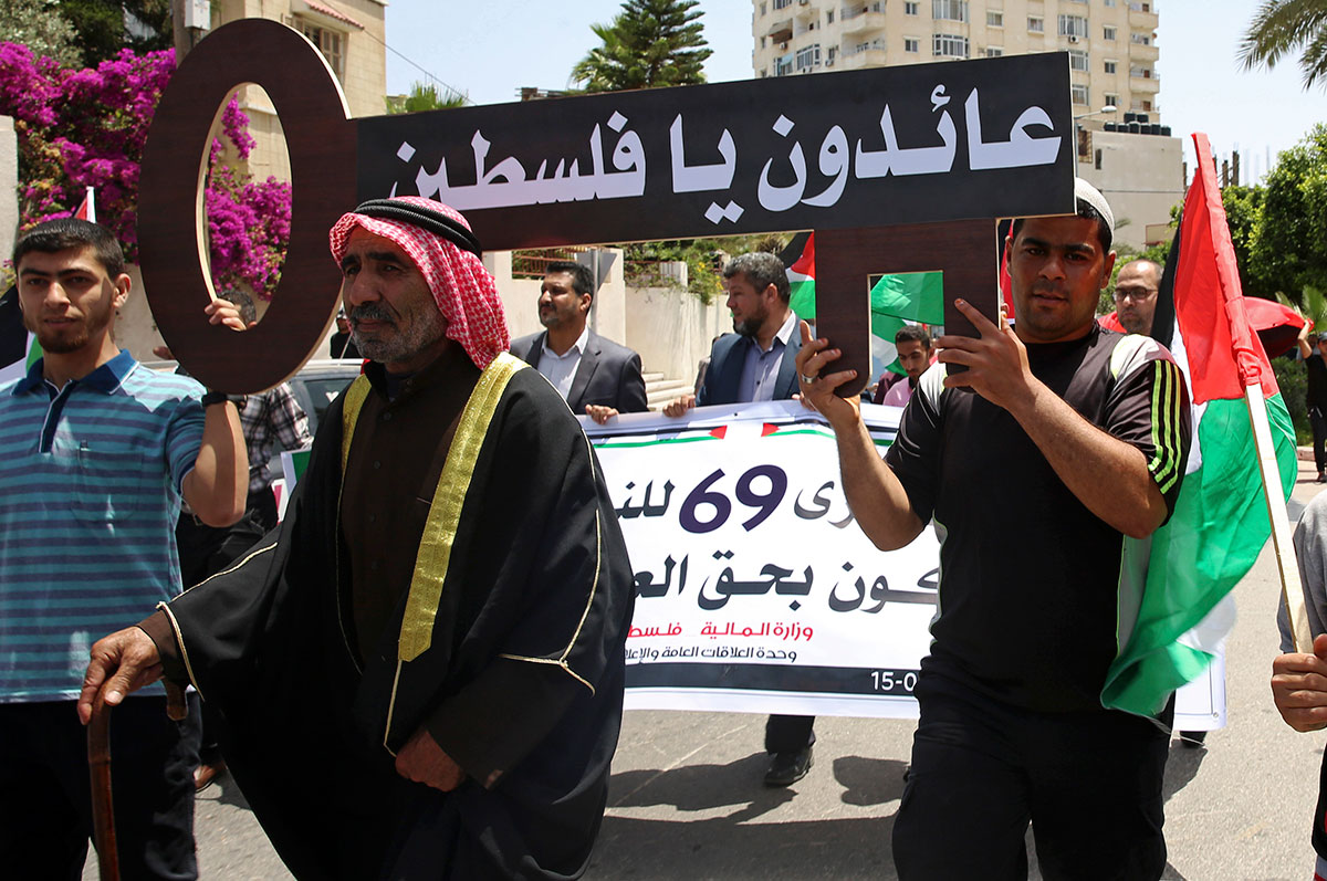 Palestinians carry a symbolic key with Arabic text that reads: 'We are coming back, Palestine' on Nakba Day in Gaza City. [Adel Hana/AP]