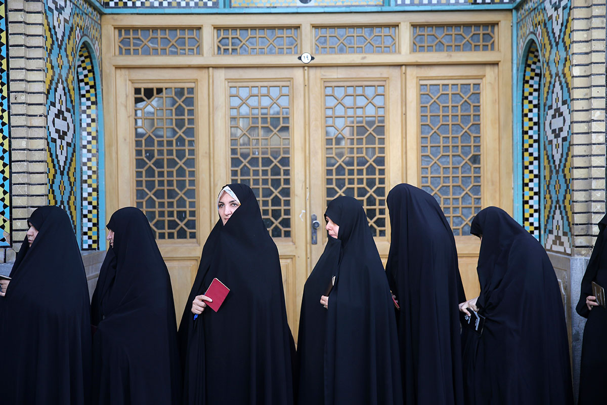 Female voters queue at a polling station for presidential and municipal elections in Qom, 125km south of Iran's capital Tehran. Iranians began voting on Friday in the country's first presidential election since its nuclear deal with world powers. [Ebrahim Noroozi/AP Photo]