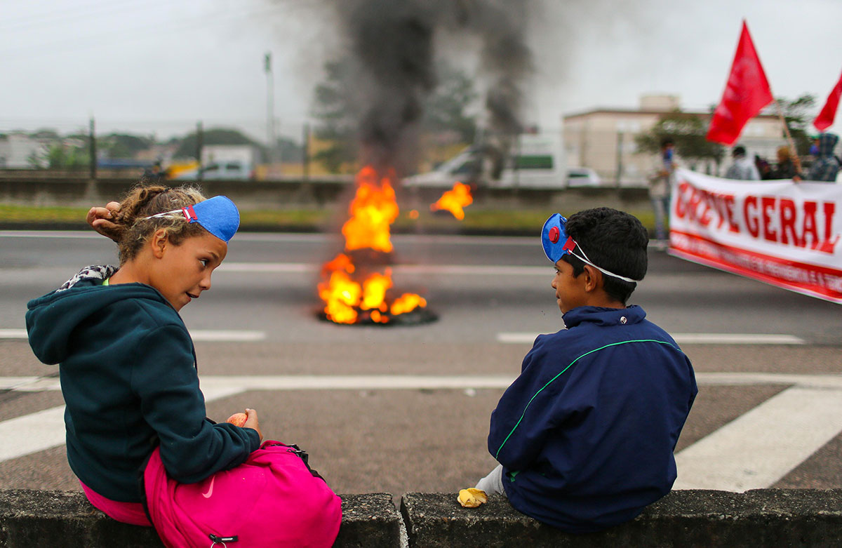 Children stand near a barricade on Dutra road in Sao Jose dos Campos during a protest against President Michel Temer's proposed reform of Brazil's social security system. [Roosevelt Cassio/Reuters]