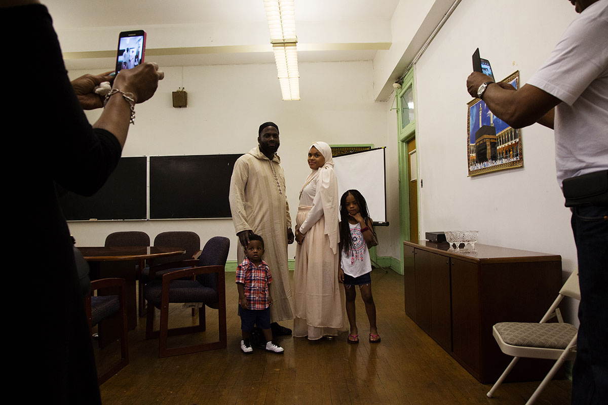 Yaseen, left, and Samiah stand, as family members take pictures on mobile phones, after their wedding at Philadelphia Masjid, just hours before the start of Ramadan. That evening Muslim residents of the city watched for the sighting of the moon, which officially marked the beginning of the holy month. [Annie Risemberg/Al Jazeera]