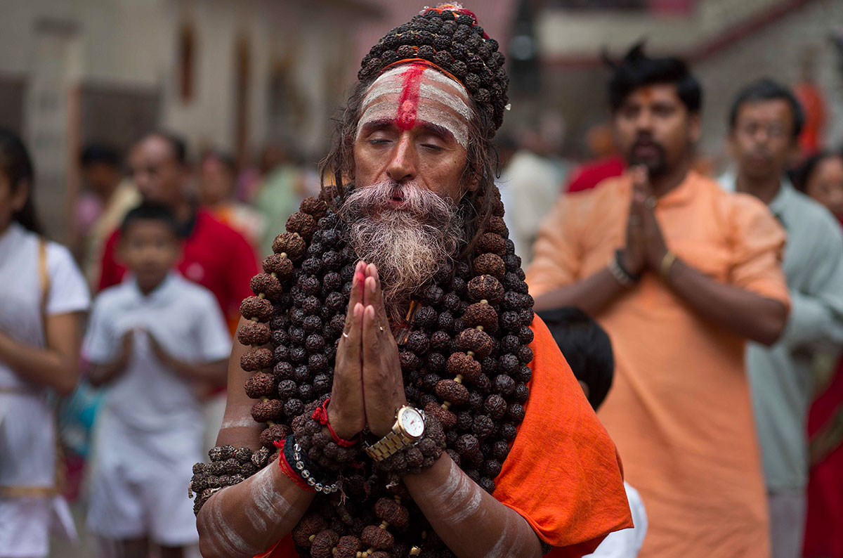 An Indian Sadhu Or Hindu Holy Man Performs Yoga As Others Follow During The International