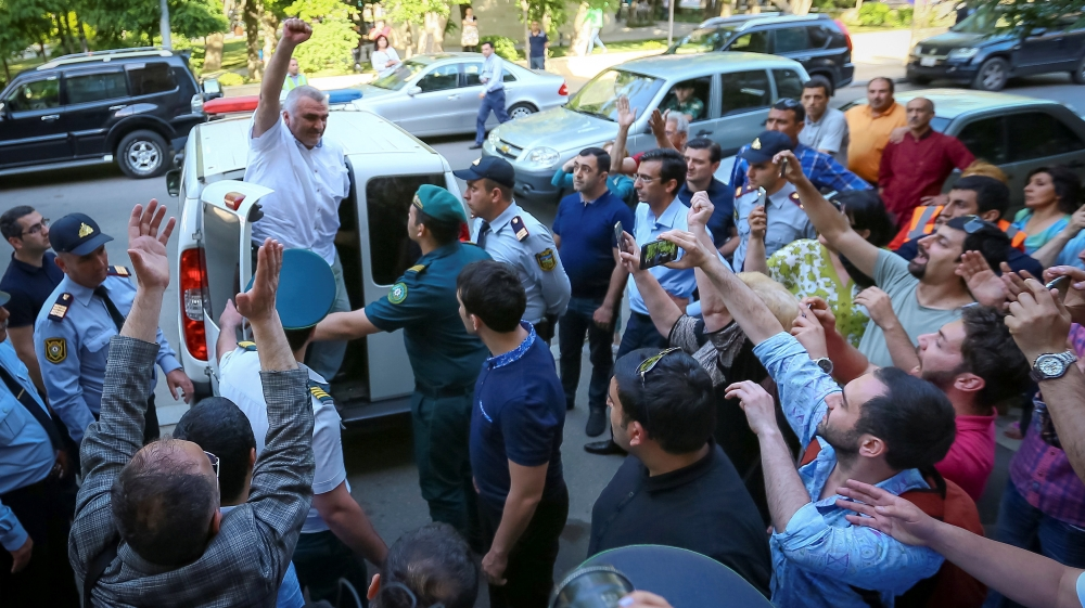 Azerbaijani Journalist Afgan Mukhtarli greets supporters as he is taken to the court in Baku