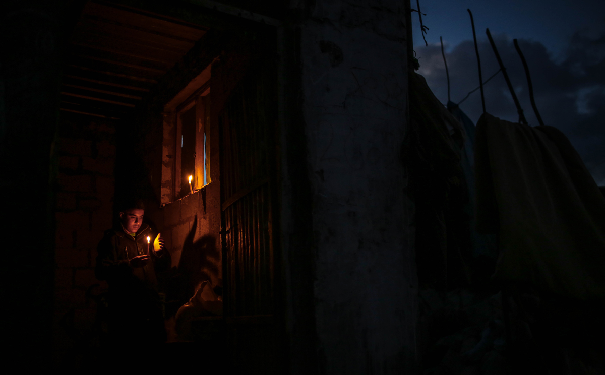 Many residents rely on candles and generators to supply light and power. [Ezz Zanoun/Al Jazeera]