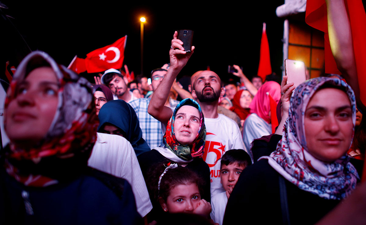 People listen to the speech of Turkey's President Tayyip Erdogan during a ceremony marking the first anniversary of the attempted coup at the Bosphorus Bridge in Istanbul, Turkey. [Osman Orsal/Reuters]