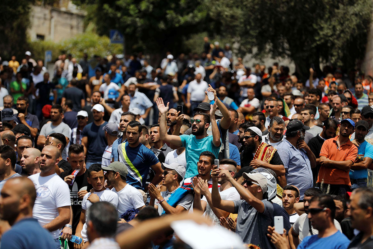 Palestinians shout slogans as they protest outside Jerusalem's Old city. [Ronen Zvulun/Reuters]