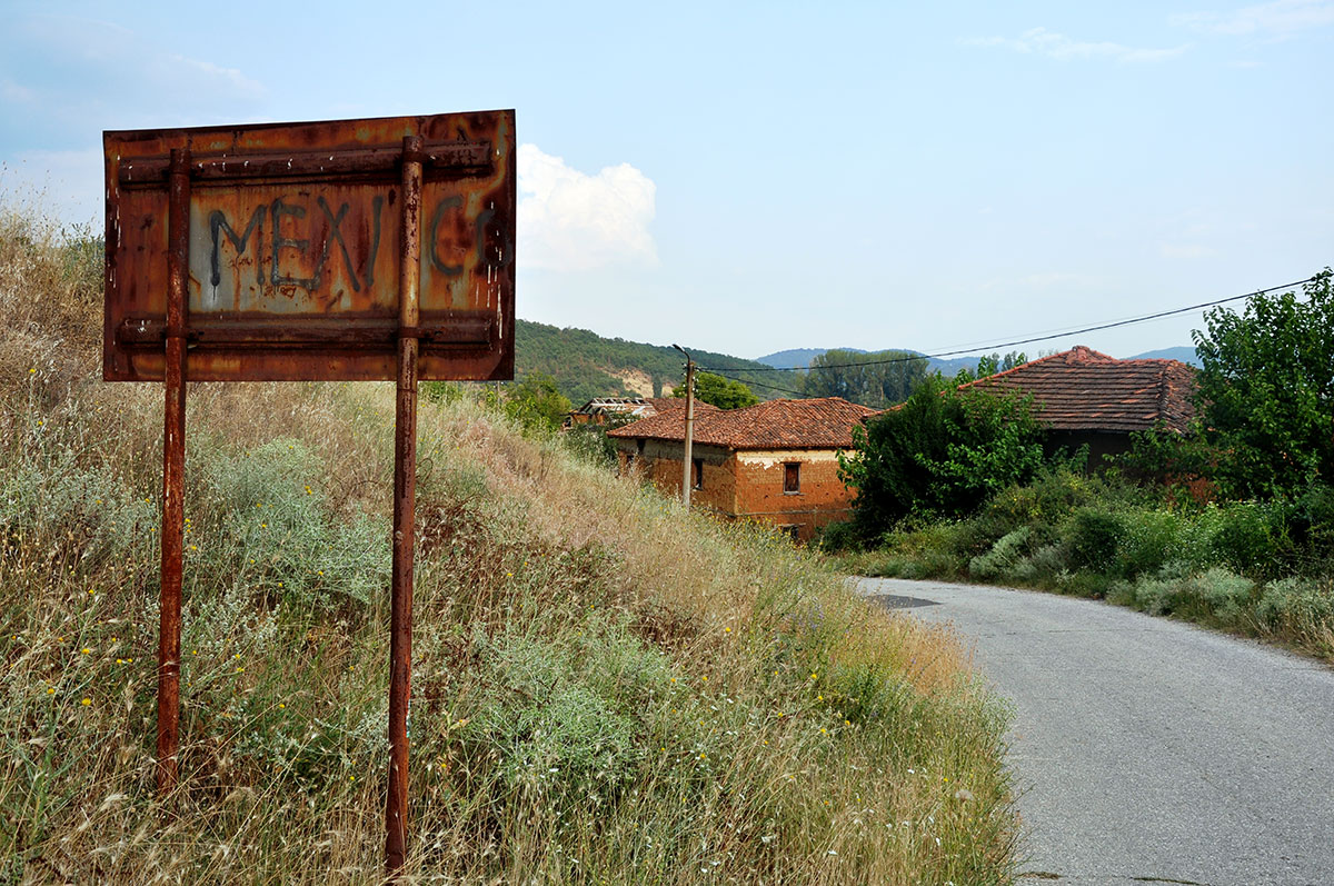 Bulgaria has been massively affected by rural depopulation. Many villages are practically deserted, derelict and desolate. On the rusty sign at the entrance to Odrintsi, someone has scribbled the word 'Mexico'. [Thomas Bruckner/Al Jazeera]