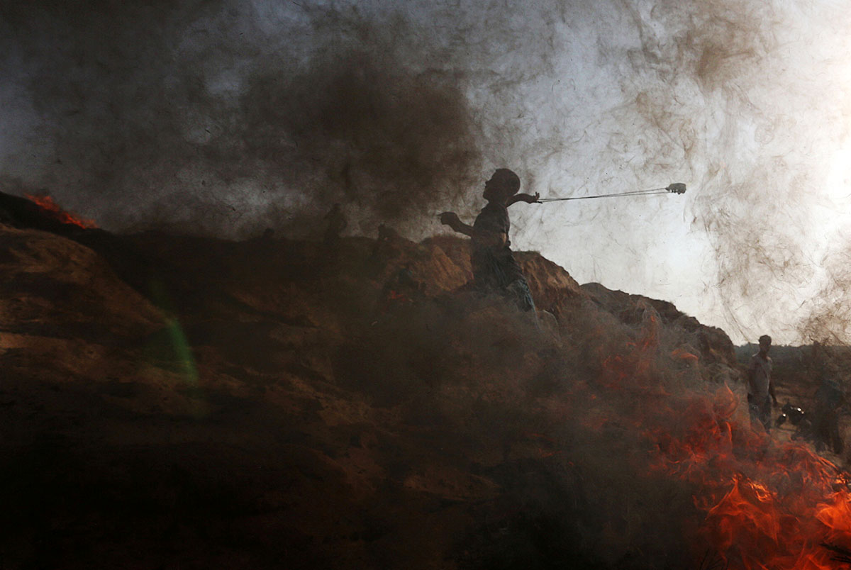 A Palestinian protester is seen amid smoke during clashes with Israeli forces near the border between Israel and the occupied Gaza Strip. [Ibraheem Abu Mustafa/Reuters]