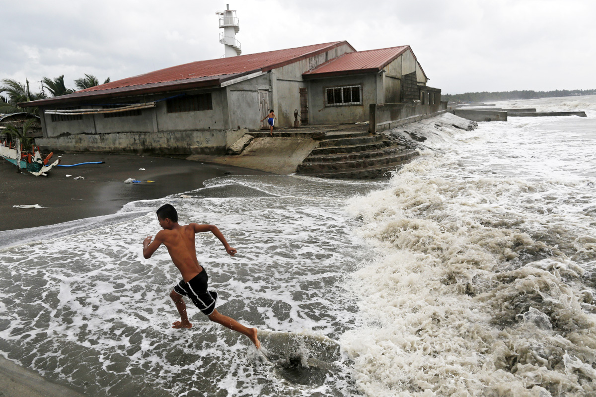 Filipino villagers take advantage of the waves from Tropical Storm Haitang. [Francis R Malasig/EPA]