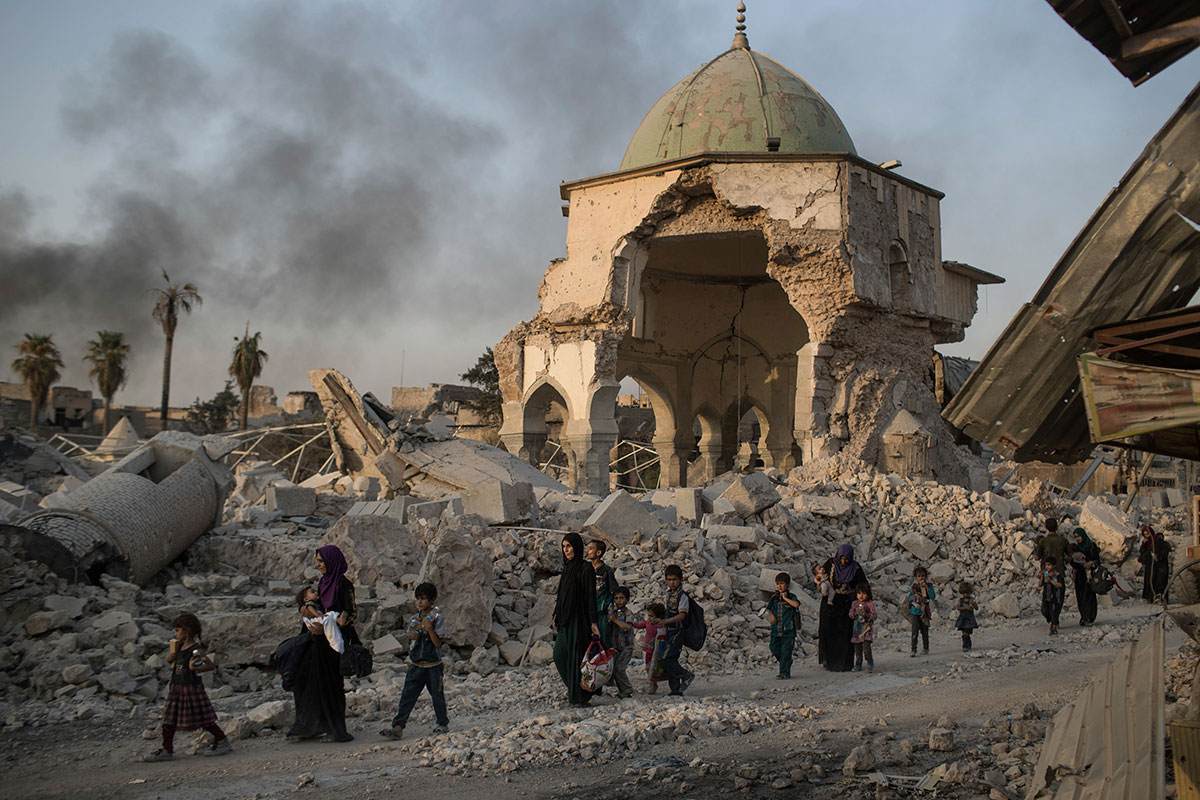 Fleeing Iraqi civilians walk past the heavily damaged al-Nuri mosque as Iraqi forces continue their advance against ISIL in the Old City of Mosul, Iraq. [Felipe Dana/AP Photo]