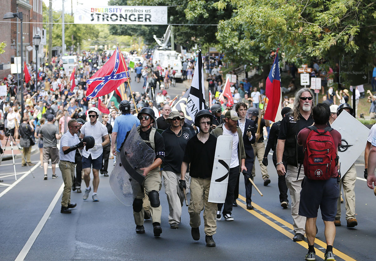 White supremacists walk through the town after their rally was declared illegal near Lee Park in Charlottesville. [Steve Helber/AP Photo]