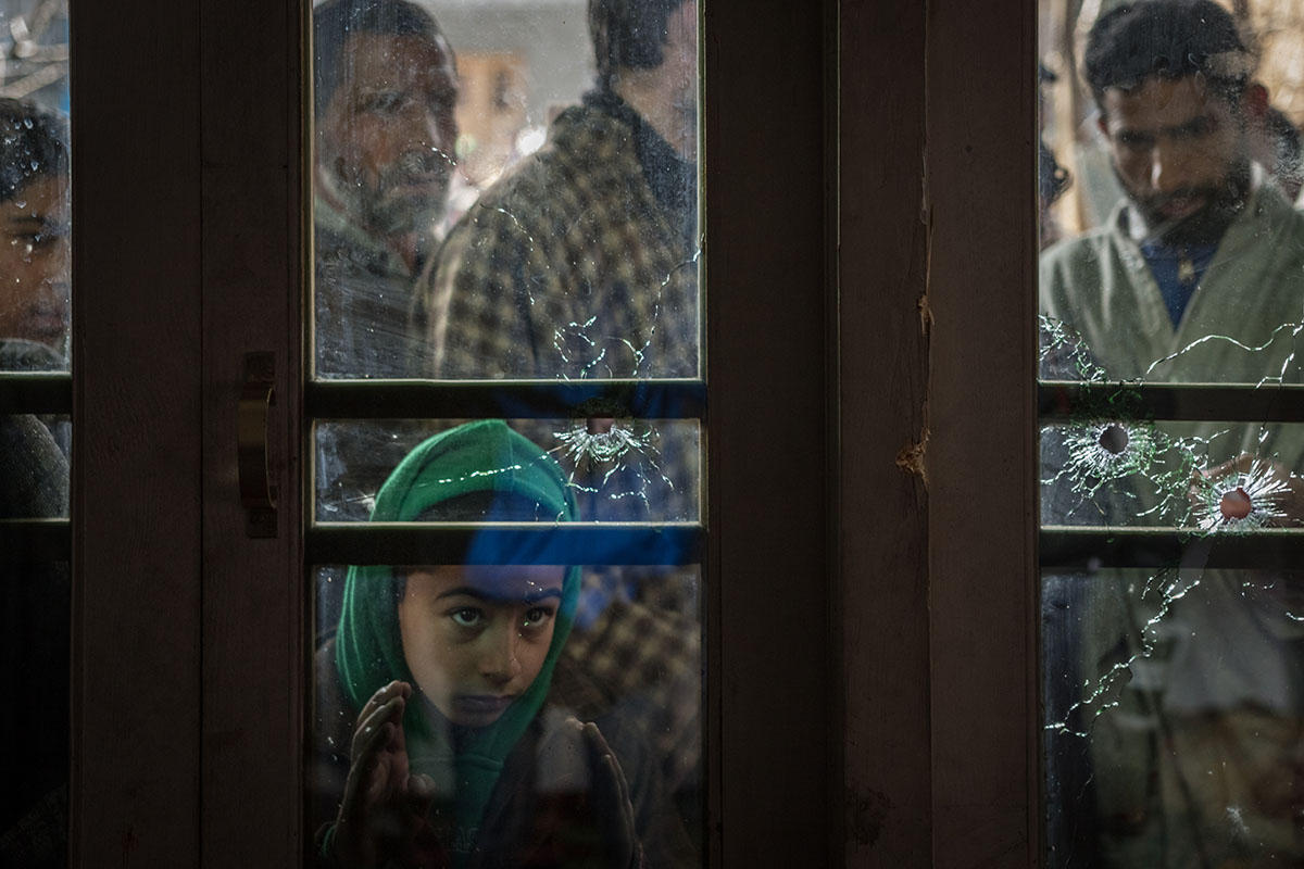 A Kashmiri boy peeks through the bullet-riddled window in the village of Moul, district of Shopian, in Indian-administered Kashmir where an overnight shoot-out between Kashmiri fighters and an Indian army convoy resulted in the deaths of one elderly Kashmiri woman and three Indian soldiers. According to witnesses, a group of rebel fighters tossed grenades and sprayed military vehicles and soldiers with bullets as the convoy crossed the village. [Violeta Santos Moura/Al Jazeera]
