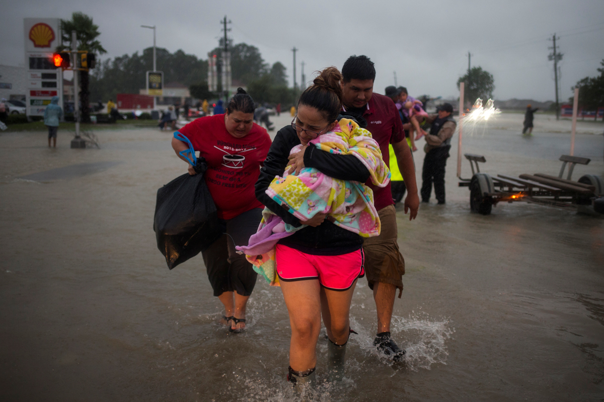 A family arrives to high ground after they fled their home due to floods caused by Tropical Storm Harvey along Tidwell Road in east Houston, Texas, US. [Adrees Latif/Reuters]