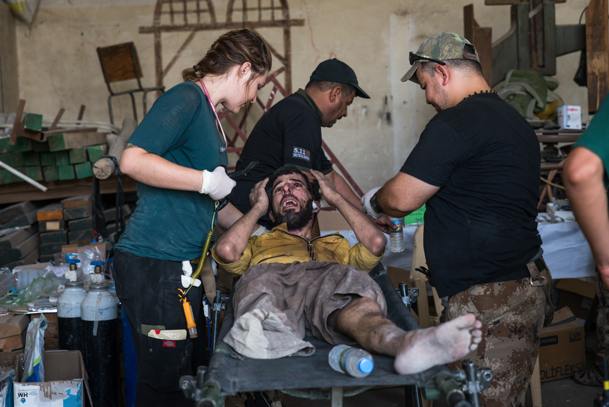 Kyirsty Unger, an American nurse and volunteer medic, treats an injured man at a trauma stabilisation point on the edge of Mosul's Old City. [Claire Thomas/Al Jazeera]